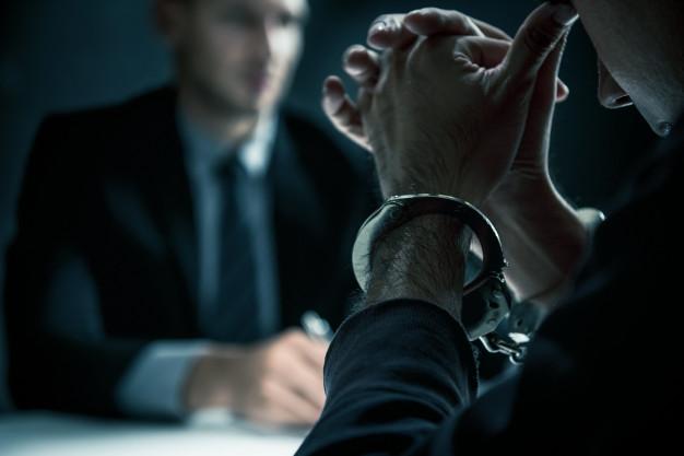 hombre-criminal-esposas-sala-interrogatorios